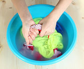 Hand washing in plastic bowl on wooden table close-up — Stock Photo