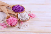 Wooden spoons with sea salt, on color wooden background — Zdjęcie stockowe
