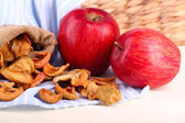 Dried apples and fresh apples, on napkin, on white wooden background — Stock Photo