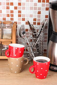 Cups and coffee maker in kitchen on table on mosaic tiles background — Stock Photo