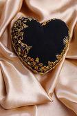 Decorative black heart, on color fabric — Stock Photo