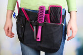 Woman hairdresser with tool belt on bright background — Stock Photo
