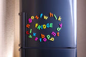 Word Fridge spelled out using colorful magnetic letters on refrigerator — Stock fotografie