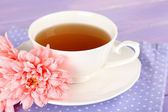 Pink chrysanthemums and cup of tea on wooden table — Stock Photo