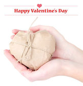 Woman hands holding a heart wrapped in brown kraft paper, isolated on white — Stockfoto