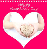 Woman hands holding heart wrapped in brown kraft paper on pink background — Stockfoto