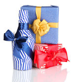 Bottle packed in gift paper with gifts isolated on white — Stock Photo