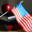 Composition of American flag, books and apple on wooden table, on dark background — Stock Photo