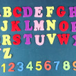 English alphabet and numbers on school desk background — Stock Photo