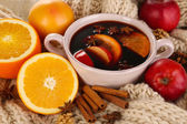 Fragrant mulled wine in pan on knitted scarf close-up — Stock Photo