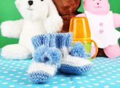 Composition with crocheted booties for baby, bottle, toy and other things on color background — Zdjęcie stockowe