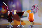 Glasses of tasty cocktails on bright background — Stock Photo