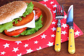 Tasty sandwich with cutlet, on color plate, on napkin, on wooden background — Stock Photo