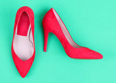 Beautiful red female shoes, on green background — Stock Photo