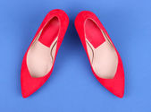 Beautiful red female shoes, on blue background — Stock Photo