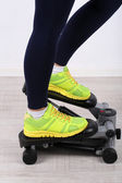 Woman doing exercise on stepper. Close-up on legs. — Stock Photo