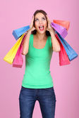 Beautiful young woman holding shopping bags on pink background — Stock Photo