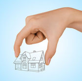 Human hand holding house sketch project on blue background — Stock Photo
