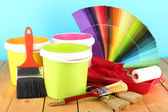 Paint pots, paintbrushes and coloured swatches on wooden table on blue background — Stock Photo
