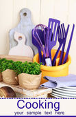 Plastic kitchen utensils in cup on wooden table — Stock Photo