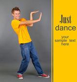 Bel giovanotto ballando su sfondo grigio — Foto Stock