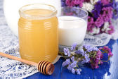 Honey and milk on blue wooden table close-up — Stock Photo