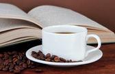 Tasse kaffee mit kaffeebohnen und buch auf holztisch auf braunen hintergrund — Stockfoto