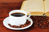 Cup of coffee with coffee beans and book on wooden background — Stock Photo