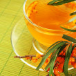 Branches of sea buckthorn with tea on bamboo background — Stock Photo