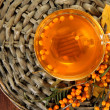 Branches of sea buckthorn with tea on wicker stand on wooden background — Stock Photo #38790653