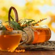 Branches of sea buckthorn with tea and jam on table on bright background — Stock Photo