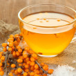 Branches of sea buckthorn with tea and sackcloth on wooden background — Stock Photo