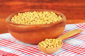 Soy beans on table on wooden background — Stock Photo