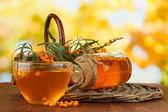 Zweige der sanddorn mit tee und marmelade auf tisch mit hellem hintergrund — Stockfoto