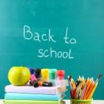 School supplies on table on blackboard background — Stock Photo #38812813