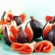Tasty figs with ham on table — Stock Photo