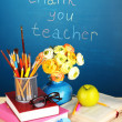 Stock Photo: School supplies and flowers on blackboard background with inscription Thank you teacher
