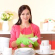 Beautiful young woman wipes clean utensils in kitchen — Stock Photo #38815609