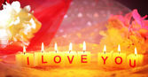 Candles with printed sign I LOVE YOU,on color fabric background — Stock Photo