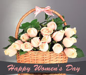 Beautiful bouquet of roses in basket on grey background — Stock Photo