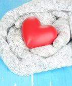 Mujer las manos en guantes con el corazón en el fondo de madera — Foto de Stock