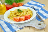 Ruddy fried potatoes on plate on wooden table close-up — Stock Photo