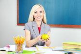 School teacher with apple sitting at table on blackboard background — Stock Photo