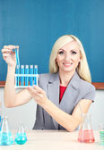 Chemistry teacher with tubes sitting at table on blackboard background — Stock Photo