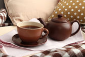 Cup and teapot on tray on bed close up — Stock Photo