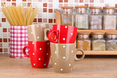 Cups in kitchen on table on mosaic tiles background — Stock Photo