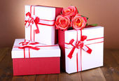 Beautiful gift boxes with flowers on table on brown background — Stock Photo