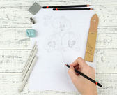 Hand draws a sketch with professional art materials, on wooden table — Photo