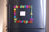 Colorful magnetic letters on refrigerator — Stock Photo