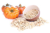 Pumpkin seeds in bowl with pumpkins isolated on white — Stock Photo